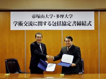 がっちりと握手を交わす帝塚山大学 山本学長(左)と多摩大学 寺島学長(右)