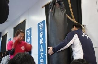 サンドバックを前に気合が入る山崎さん(左)