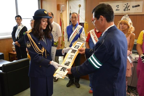 奈良西警察署・西本署長より一日警察署長の委嘱状とタスキを受け取る