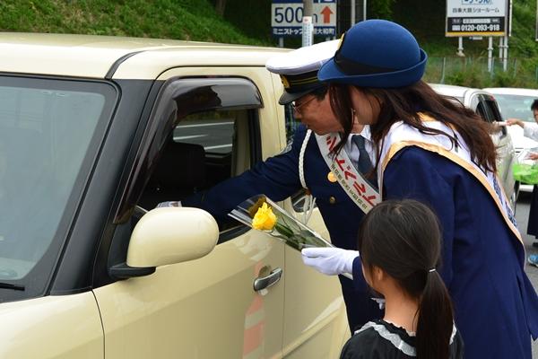 警察署前を通るドライバーにシートベルト着用徹底の呼びかけとバラのプレゼント(西本署長と)