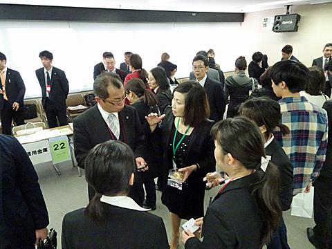 出展企業の方と意見を交わす菅准教授と学生たち
