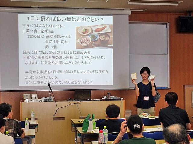 1日の食事バランスについて食品模型を用いて解説する百木講師